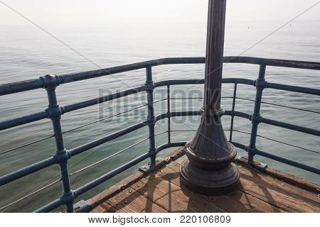 Blue painted railing and light post on the corner of a pier overlooking the ocean on a hazy day, horizontal aspect