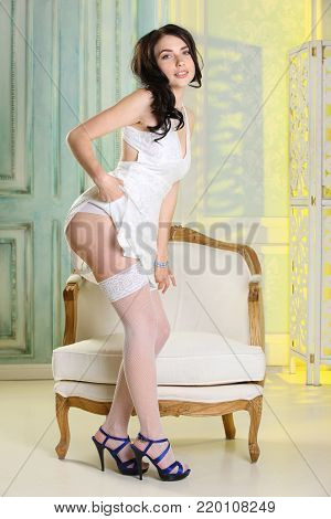Adorable happy brunette girl in short white dress and white stockings posing in full length on high heels. Attractive partially naked female body.