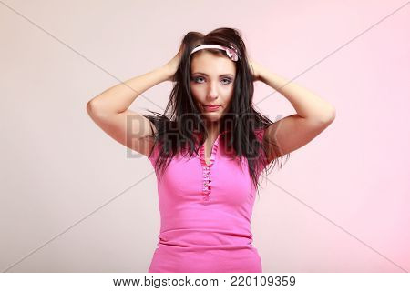 Portrait of childish young woman with headband. Infantile girl messing up her hair on pink. Longing for childhood. Studio shot.