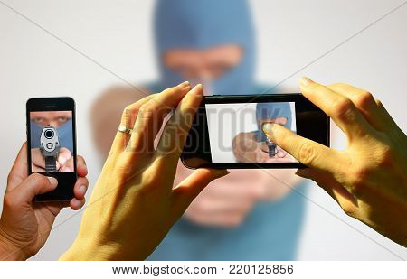 a rubbernecker photographing with mobile phones a bank robber with pistol