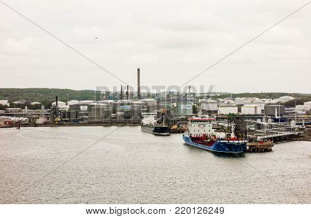 GOTHENBURG, SWEDEN - MAY 16, 2017: Two small tanker ships are docked near storage tanks in Gothenburg harbor.