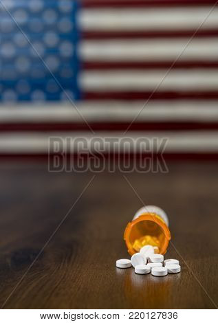 Oxycodone is the generic name for a range of opoid pain killing tablets. Prescription bottle for Oxycodone tablets and pills on wooden table with USA flag in background