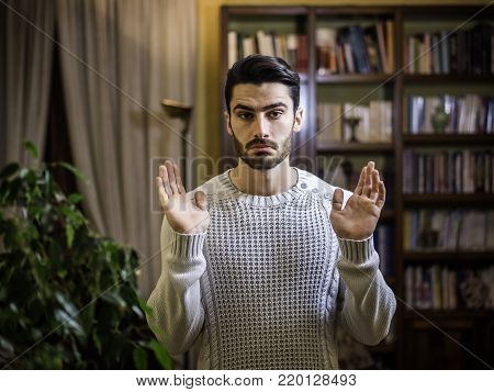 Confused or doubtful or innocent young man shrugging with palms open, indoor shot in a house