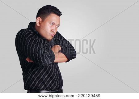 Portrait of funny Asian man showing cynical unhappy angry facial expression, looking to the side, crossed arms, isolated on grey