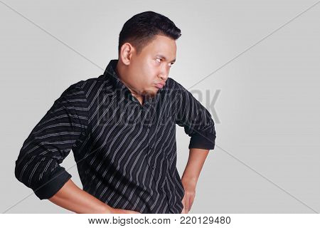 Portrait of funny Asian man showing cynical unhappy angry facial expression, looking to the side, hands on hip, isolated on grey