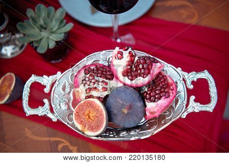 Silver serving dish with fresh pomegranate and figs and French macarons served on a table with red cloth and candles