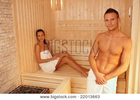 Portrait of couple in sauna on wellness weekend, smiling at camera.?