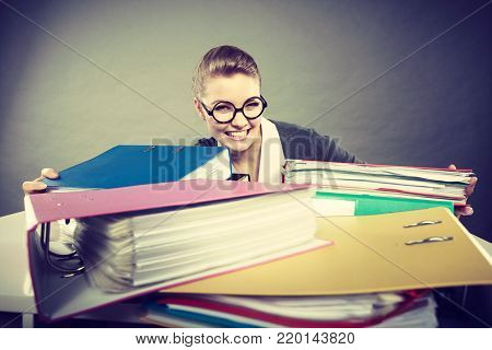 Happiness and satisfaction from working. Young positive happy blonde accountant at work. Lovely woman surrounded of piles of colorful binders.