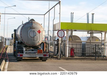 Fuel Tanker Truck at the Gas Station. The worker prepares the device for pumping of gasoline