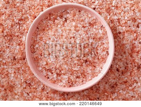 Pink Himalayan salt in the small pink bowl. A small pink bowl full of salt crystals.
