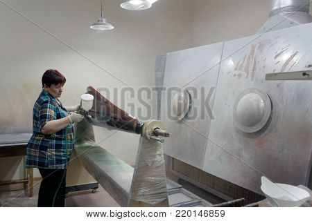 ST. PETERSBURG, RUSSIA - AUGUST 8, 2017: Female worker varnishing the soundbox of harp using spray gun in Resonance Harps enterprise. It revives the production of harps of the Lunacharsky factory