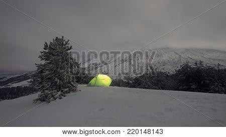 illuminated tent on the snow in alpine tree line under Etna Mount, Sicily