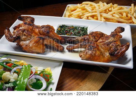 Roasted cockerel with potato chips and salad