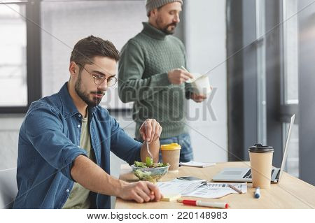 Two Successful Businessmen Work Together At Office, Study Documents And Arrange Meeting With Partner
