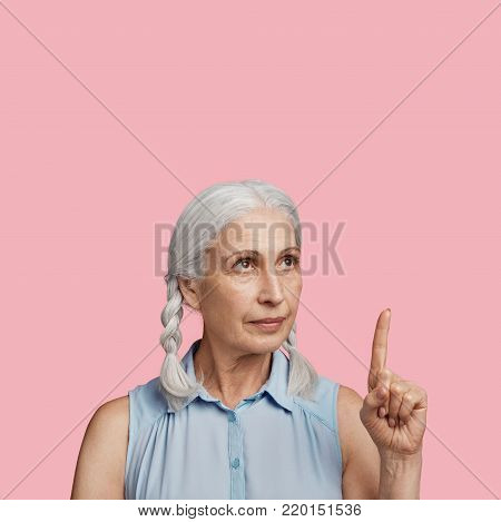 Positive Smiling Woman With Grey Plaits, Dressed In Blouse, Indicates With Fore Finger At Blank Copy