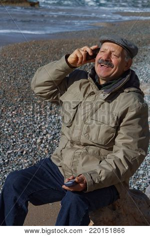 Senior man on the beach talking by mobile phone and holding a second phone in his hand