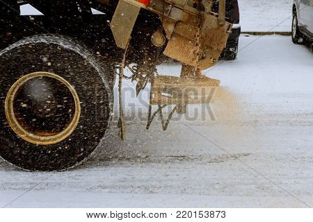 working Big red snowplow sands carriageway during snowfall and ice