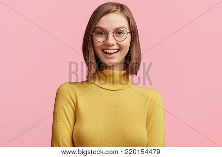 Positive Attractive Young Model Wears Casual Yellow Turtleneck Sweater And Round Glasses, Being Happ