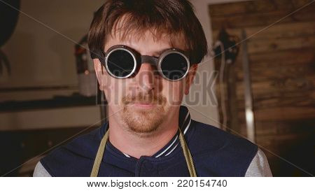 Portrait of man industrial welder in protective glasses looking at camera, .