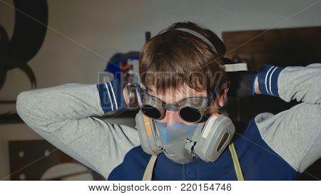Portrait of blacksmith in protective glasses dresses respirator at his workshop