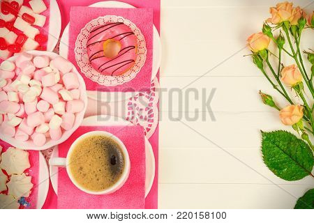 Cup of coffee, donut, tasty snacks and flowers, top view, flat lay.