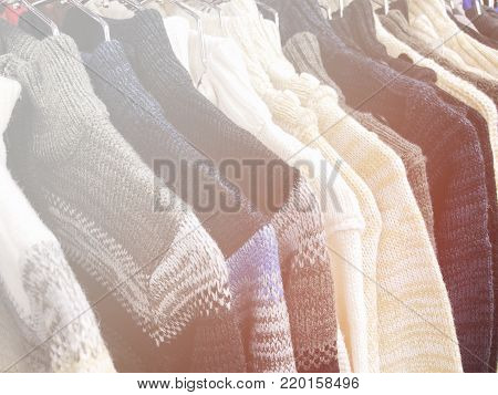 Womens sweaters on the hanger in the store. Clothes hang on a shelf in a clothes store