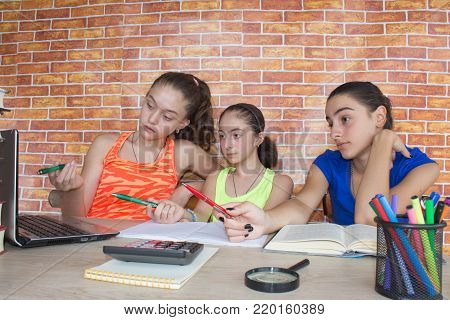 Three girls sitting at desk at home, doing homework. Thoughts, education, creativity concept. Portrait of Three pretty girls high school student studying