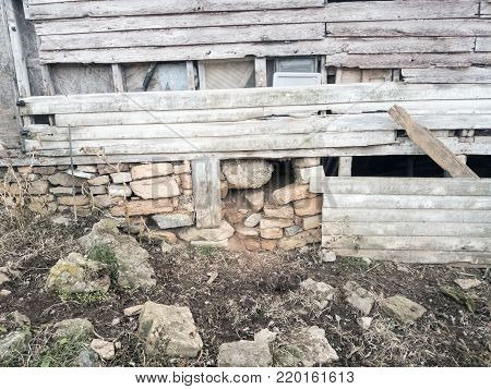 Closeup of abandoned, dilapidated farm house exterior wall with stone foundation