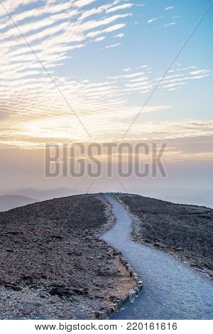 Vertical photo colorful landscape view on judean desert land with magic sky on background and color clouds. Beautiful nature with mountains, rocks, sand and ruins in holy land in Israel.