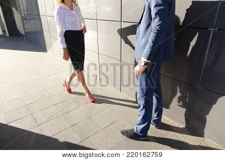 Young beautiful girl goes to meet, suited to young man, businessman, and they communicate, share ideas, smile, laugh, talk, solve problems on background of business center on open air. Guy dressed in blue classic suit, white shirt with tie and blue shoes,