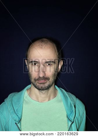Vertical portrait of the unshaven middle aged man with intent look