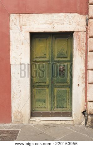 Wooden italian door with marble decoration in Tuscany