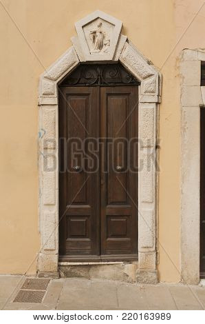 Wooden italian door with marlbe decorations in Tuscany