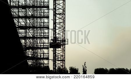 silhouette scaffolding building construction with copy space for text, black profile structure of scaffolding warm colors sunset in the city, architecture engineering work