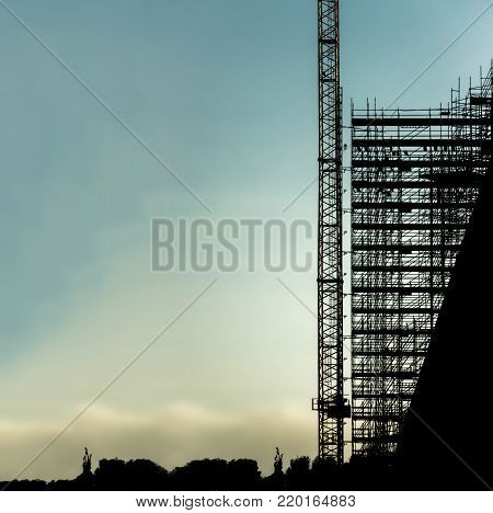 silhouette scaffolding building construction crane with copy space for text, black profile structure of scaffolding sunset at city, architecture engineering diagonal building structure