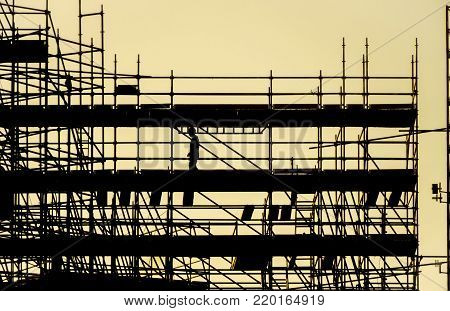 silhouette of worker at scaffolding, working day at building construction, profile structure of scaffolding warm colors of orange sunset, construction, architecture and engineering work