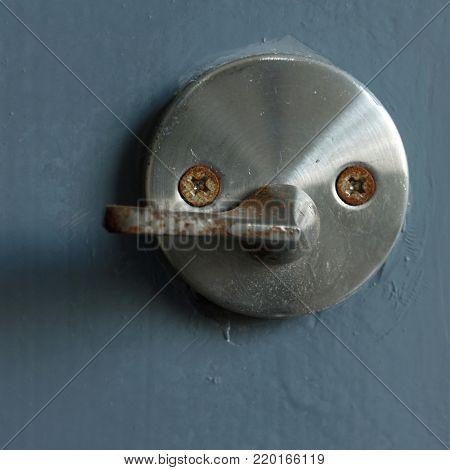 Anthropomorphic door lock and lever in shape of a face on wooden door.