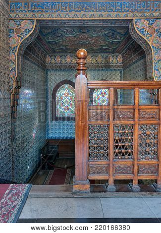 Cairo, Egypt - December 2, 2017: Wooden staircase, decorated wooden balustrade, Turkish ceramic tiles wall, ornate ceiling, stained glass windows, Residence hall at Manial Palace of Prince Mohammed Ali