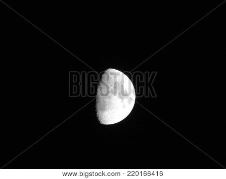 half moon with moon seas in the night sky