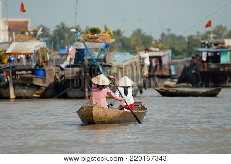 CAI BE, VIETNAM - FEBRUARY 16, 2007: Unidentified women cross Mekong river by paddleboat at the famous floating market in Cai Be, Vietnam. Cai Be is often called the