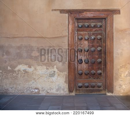 Grunge wooden aged door on grunge stone wall, Medieval Cairo, Egypt