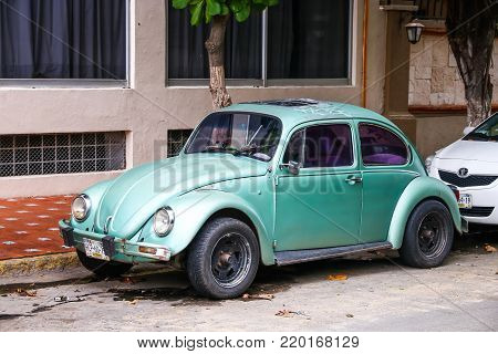 Acapulco, Mexico - May 30, 2017: Green retro car Volkswagen Beetle in the city street.