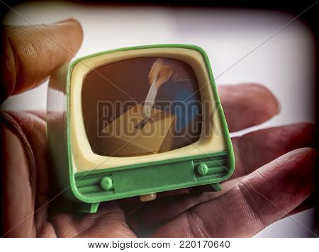 Miniature TV on one hand, voting urn appears on the screen, conceptual image