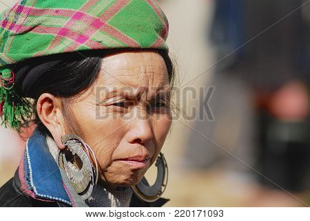 SAPA, VIETNAM - FEBRUARY 10, 2007: Portrait of an unidentified Black Miao (Hmong) minority woman wearing traditional costume with silver earrings at the street in Sapa, Vietnam.