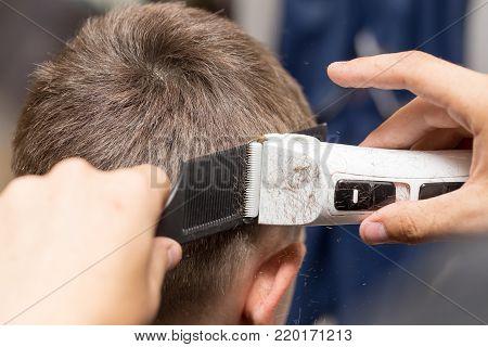 Man having a haircut with a hair clippers .