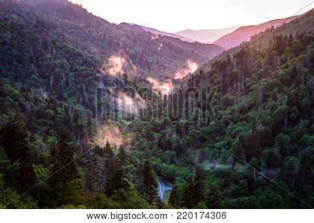 Winding Mountain Road. Mists rises from a mountain valley with a Smoky Mountain sunset in the background and winding mountain road in the foreground. Newfound Gap, Great Smoky Mountains National Park.