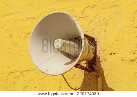 Old loud speaker on the cement wall background .