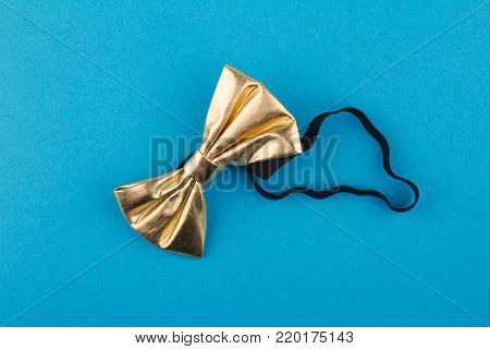 golden shinny bow tie with black textile elastic band on light blue background