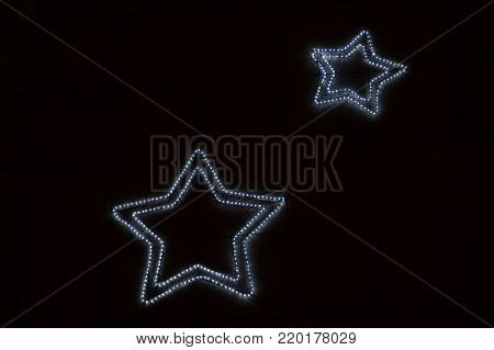 Photo of golden star with light bulbs on red velvet curtain on stage .