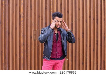 Handsome Young Arabic Male Man, Student Feels Headache, Touching Head, Trying to Ease Pain, Feels Discomfort, Standing on Background of Wooden Panel Stairs Outdoors. Confident Guy Arab Dressed in Black T-Shirt Over Maroon Shirt and Wears Black Leather Jac